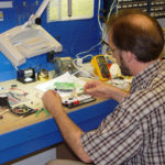 Designer using a breadboard for testing part of a product invention prototype